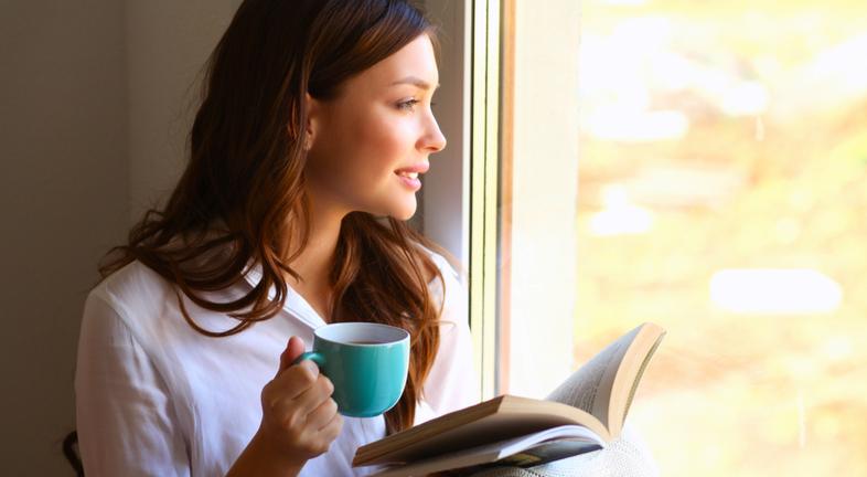 junge Frau liest buch trinkt tee fenster